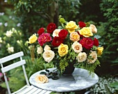 Vase of roses on marble table in garden
