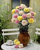 A vase of carnations on a garden table