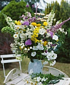 Colourful arrangement of summer flowers on garden table out of doors