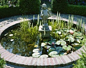 Ornamental pond with water lilies and statue