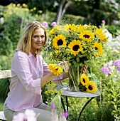 Young woman putting sunflowers in vase