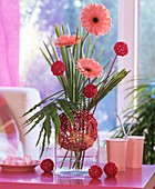Arrangement of gerberas, dwarf palm, holly fern, wicker balls