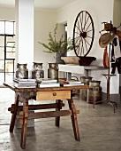 Rustikaler Holztisch mit Antiquitäten und Büchern in Wohnraum mit poliertem Betonestrich