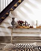 Treppennische mit rustikalem Wandtisch und einem Zebrafell als Teppich