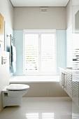 Weisses Badezimmer mit eingebauter Badewanne und glänzendem Steinboden