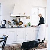 Traditionelle Küche im Landhausstil mit kochender Frau und großem, schwarzen Hund auf dem Teppich