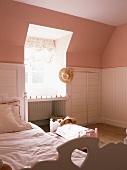 Schlafraum in Altrosa mit weisser Holzverkleidung im ausgebauten Dach