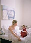 Mutter und Kind im Gespräch auf dem Bett sitzend