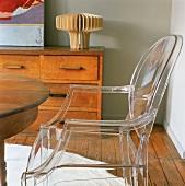 Ein Plastikstuhl neben rundem Holztisch & Schubladenkommode