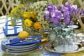 Crockery, cutlery and flowers on table out of doors