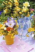 Bunches of summer flowers with sparkling wine glasses out of doors
