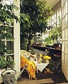 Stuhl & Tischchen am Eingang eines üppig bepflanzten Gewächshauses