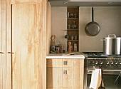 Küchenausschnitt mit Edelstahlherd & Holzschränken