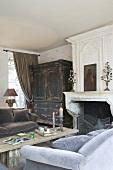 Wohnzimmer mit Kamin, altem Holzschrank & Sofas mit Samtbezug