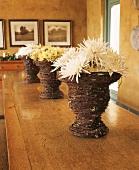 Geflochtene Dekovasen mit Chrysanthemenblüten auf altem Holztisch