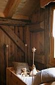 Altes Kinderbettchen aus Holz in Zimmerecke eines alten Holzhauses