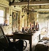 Ländlich, rustikaler Wohnraum in altem Ziegelhaus mit Kerzenbeleuchtung, Tisch, Schaukelstuhl & Strohballen als Sitzbank