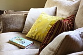 A book and a pair of glasses on a sofa