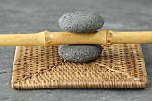 A bamboo stick between two pebbles on a place mat