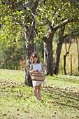 Mädchen hält Korb mit Äpfeln unter Apfelbaum