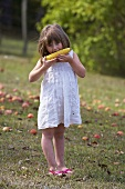 A girl eating a corn cob in a garden