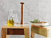 A karaffe of oil and a pepper mill standing on home-made wooden stools