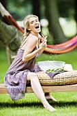 Blonde Frau bespritzt sich mit Wasser im Garten