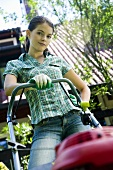 A young woman with a lawn mower