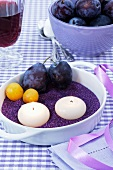 Candles, damsons and greengages on purple sand