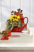 An espresso cup with sunflowers, a jug with firethorn and a raspberry sprig