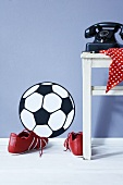 A football wall sticker, football boots and an old telephone