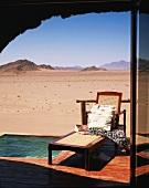 Liegestuhl auf Holzterrasse mit kleinem Pool & Fernblick auf wüstenartige Landschaft