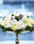 Xmas table decoration: white flowers, fir sprigs, candles, baubles