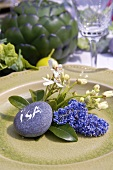 Floral decoration and pebble place card on plate