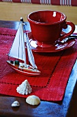 Red cup & saucer & maritime decorations on coffee table