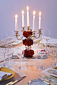 Candelabrum with red roses on table laid for special occasion