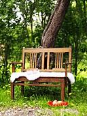Wooden bench with sheepskin in garden