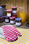 Oven mitts and jars of home-made jam