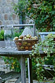 Fresh apples in basket on garden table