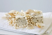 Soap with pearls and shells on white towel