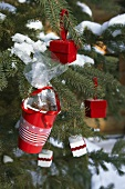 Red plastic cup containing pecan sweets on Christmas tree