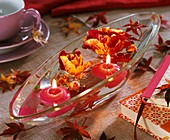 Artists' roses and floating candles in glass dish