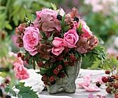 Roses, hydrangeas and blackberries in stone vase
