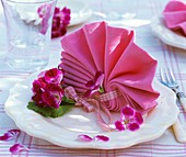 Napkin folded in the shape of a fan with geranium flowers
