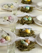 Marbled eggs in Easter nests on laid table