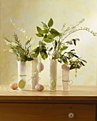 Herbs and flowering branches with Easter eggs in glasses