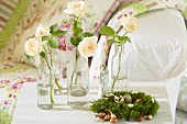 Easter nest with quail's eggs, cream coloured roses in bottles