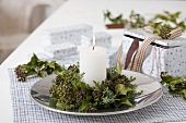 A candle with wreath of ivy and juniper