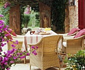 Table laid for coffee with rattan armchairs