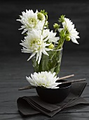 Asian place-setting with white chrysanthemums, dark background